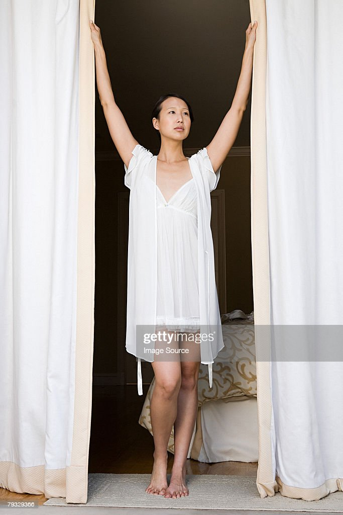 Woman opening curtains : Stock Photo