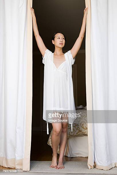 woman opening curtains - women in slips stock photos and pictures