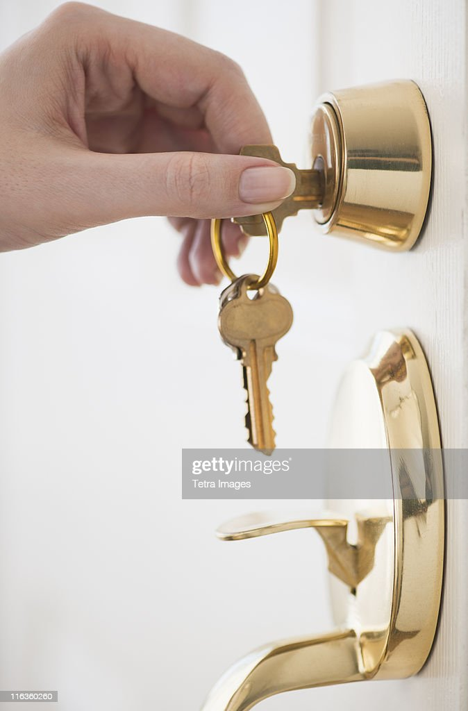 Woman opening door lock : Stock Photo