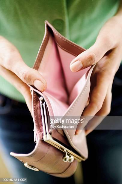 Woman opening empty wallet