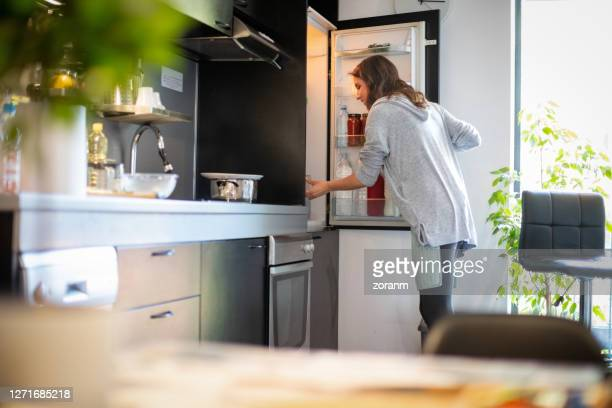 woman opening fridge to find ingredients for lunch - refrigerator stock pictures, royalty-free photos & images