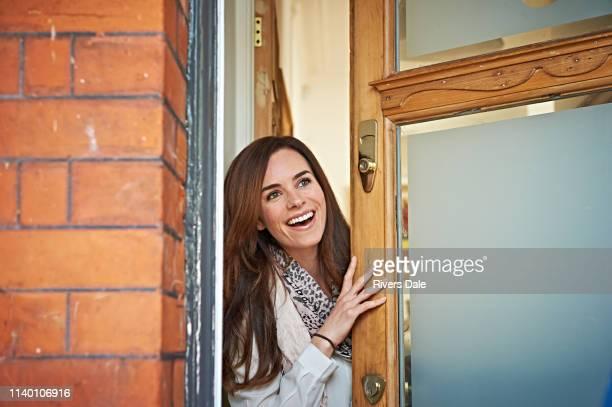 woman opening front door - front door stock pictures, royalty-free photos & images