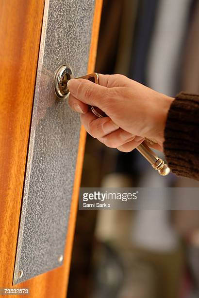 Woman opening front door with key, close-up of hand