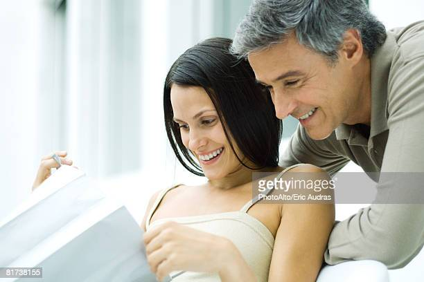Woman opening gift bag, man looking over her shoulder, both smiling