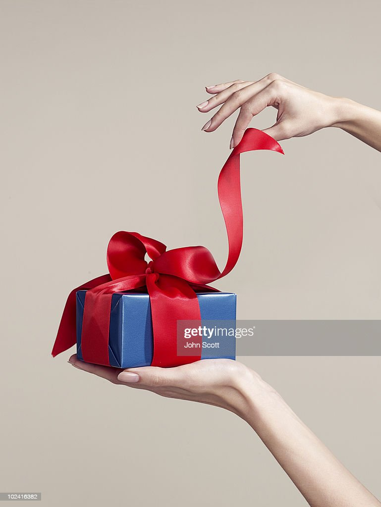 Woman opening gift, close-up of hands : Stock Photo