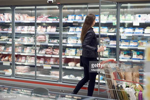 Woman opening glass door of cabinet at refrigerated section in supermarket