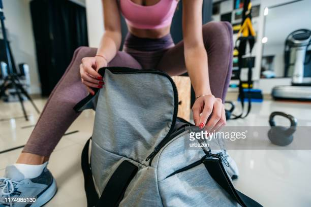 woman opening gym bag - gym bag stock pictures, royalty-free photos & images