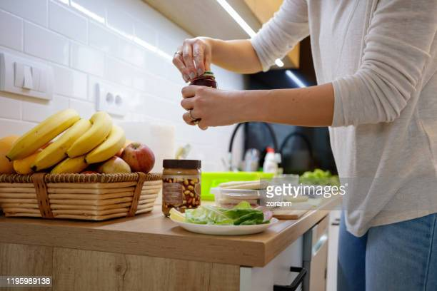woman opening jam jar - jar stock pictures, royalty-free photos & images