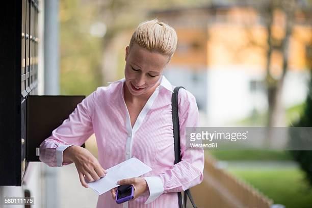 woman opening letter - bekommen stock-fotos und bilder