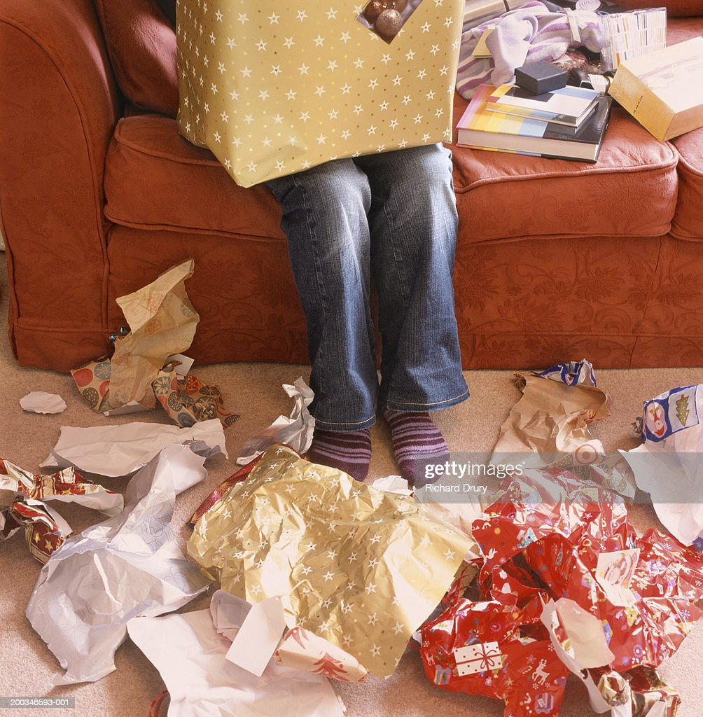 Woman opening presents, wrapping paper on floor, low section : Stock Photo