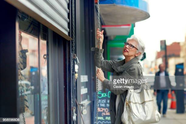 woman opening store shutter - shutter stock pictures, royalty-free photos & images