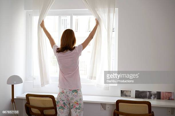 Woman opening the curtain,looking out the window