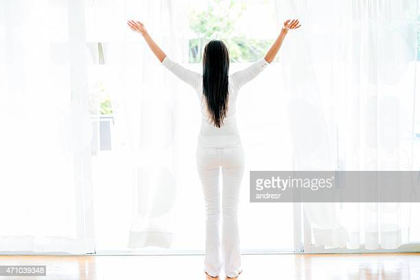 Woman opening the windows at home