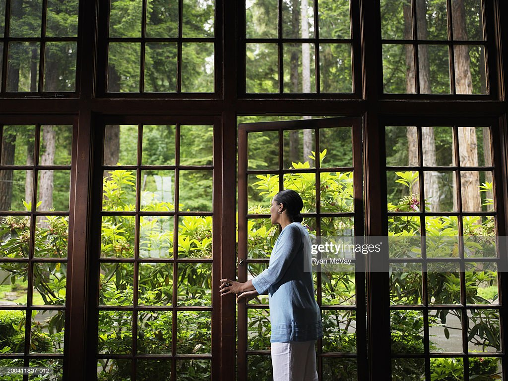 Woman Opening Window Looking Outside Smiling Side View Stockfoto