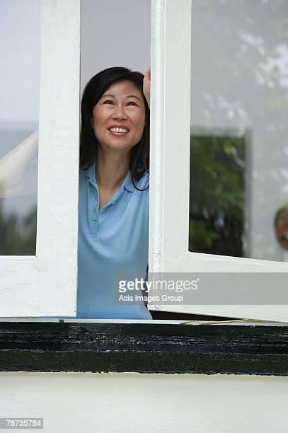 Woman opening windows, smiling