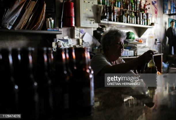 Woman opens a beer at a bar during a power outage in Caracas on March 9, 2019. - Venezuela President Nicolas Maduro claimed that a new cyber attack...