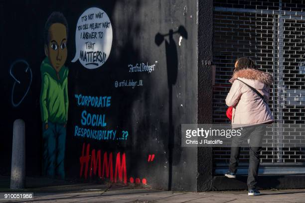 A woman opens a shop next to artwork by graffiti artist 'The Artful Dodger' on a wall in Brixton in response to an advert by clothing store HM which...