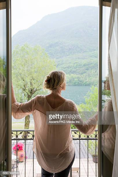 Woman opens doors onto terrace, lake