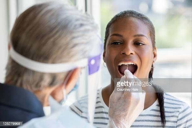 woman opens mouth for cheek and throat swab while being tested for covid-19 coronavirus - cheek stock pictures, royalty-free photos & images