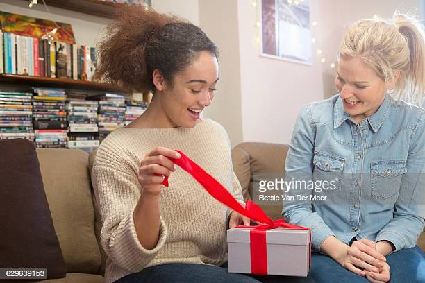 Woman opens present while friend looks on.