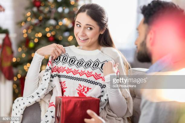 woman opens up gift containing christmas sweater - ugly christmas sweater party stock pictures, royalty-free photos & images