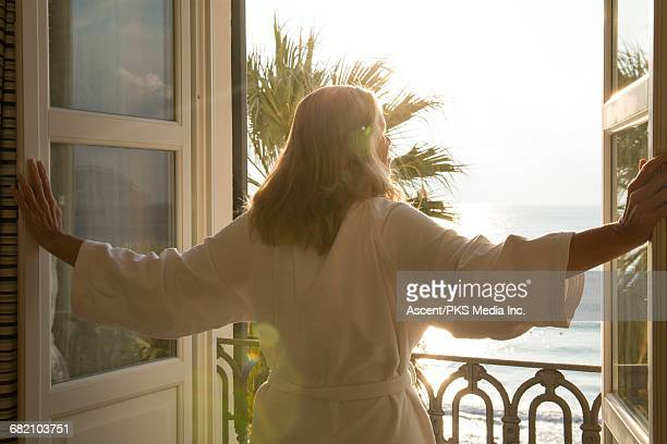 woman opens window over sea, in bath robe - viewpoint stock pictures, royalty-free photos & images
