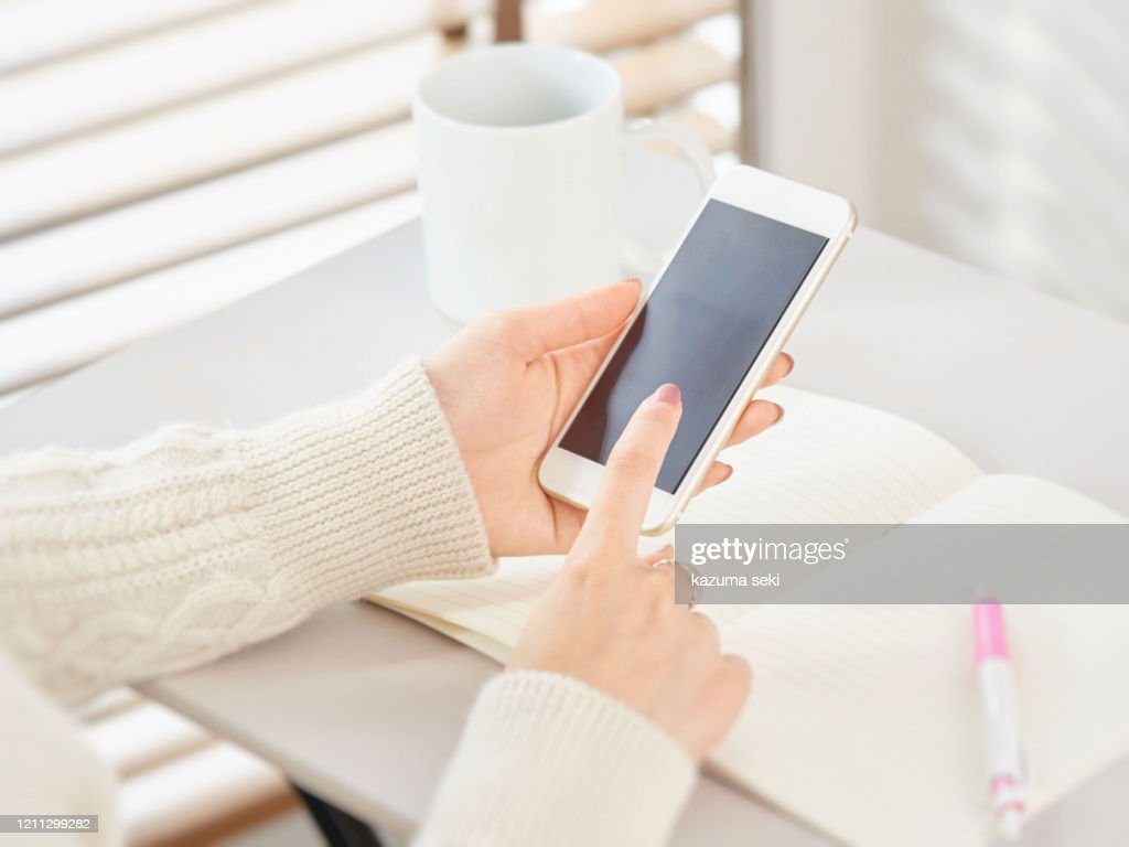 Woman operating a smartphone : Stock Photo