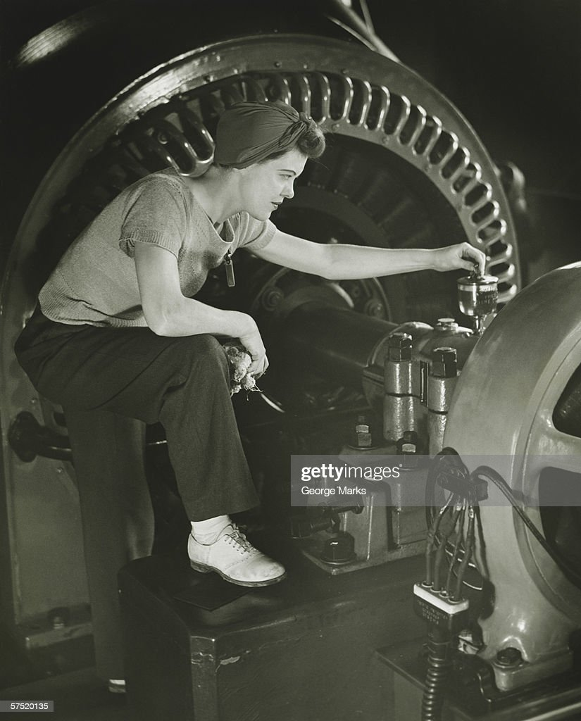 Woman operating machine in factory, (B&W) : Stock Photo