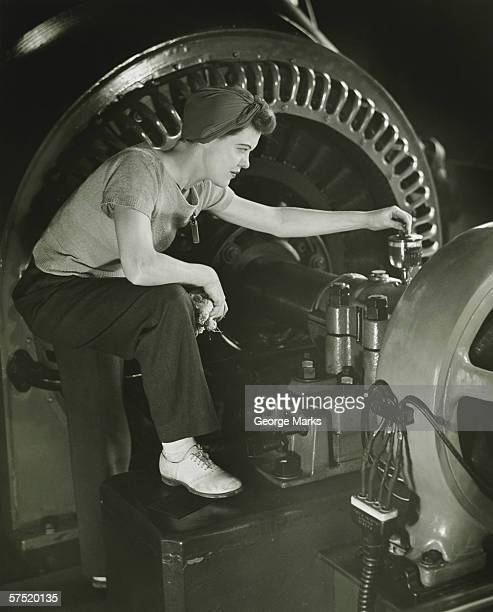 Woman operating machine in factory, (B&W)