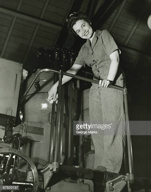 Woman operating machine in factory, (B&W), portrait, low angle view