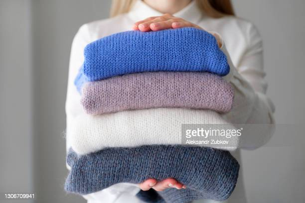 a woman or a girl holds an armful of knitted things of different colors, stacked in a pile, in the room. winter and autumn warm cozy sweaters for charity. the concept of storage, care and washing of handmade products. a copy of the text space. - cashmere stock pictures, royalty-free photos & images
