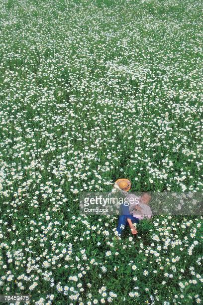 Woman or girl lying in field of flowers