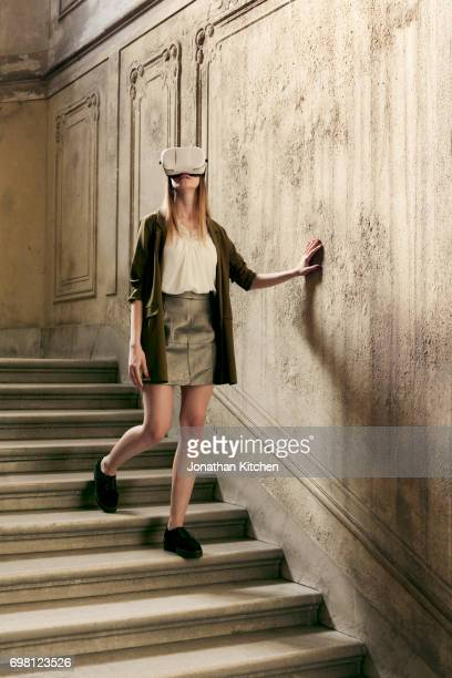 woman or young girl feels her way down the stairs of a building while experiencing virtual reality via a headset sensing her way while dressed stylish - down blouse stock photos and pictures