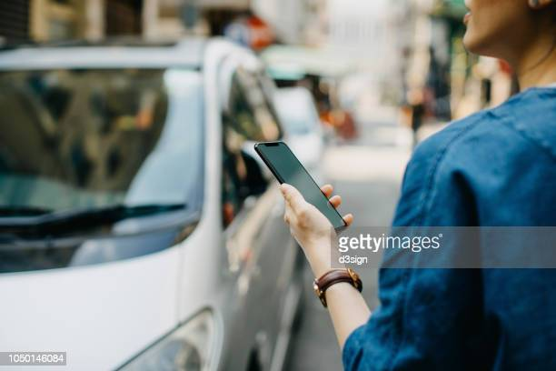 woman ordering a taxi ride with mobile app on smartphone in the city - hail stock pictures, royalty-free photos & images