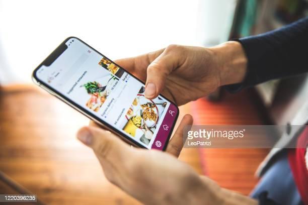 社会的な離散時間に自宅でモバイルアプリの配達によって食べ物を注文する女性 - eコマース ストックフォトと画像