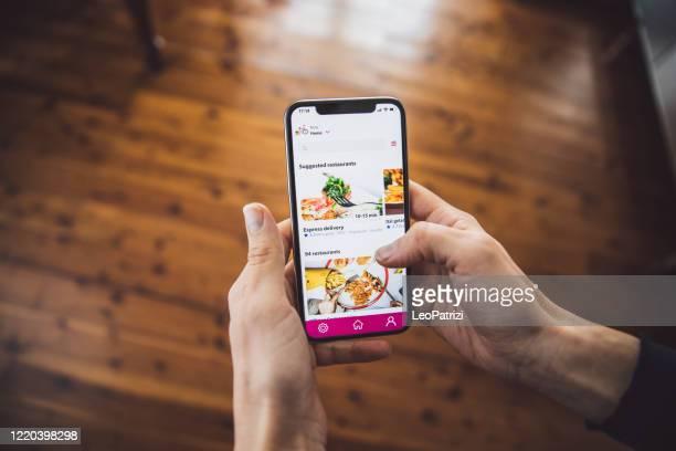 donna che ordina cibo con la consegna di app mobili a casa al momento del distanziamento sociale - software foto e immagini stock