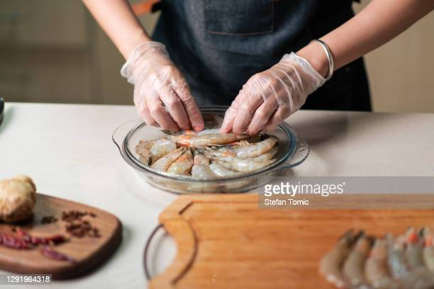 woman ordering fresh prawn for cooking in the glass bowl - raw food stock pictures, royalty-free photos & images