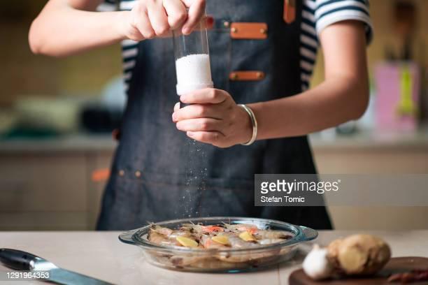 mulher pedindo camarão fresco para cozinhar na tigela de vidro - sal de cozinha - fotografias e filmes do acervo