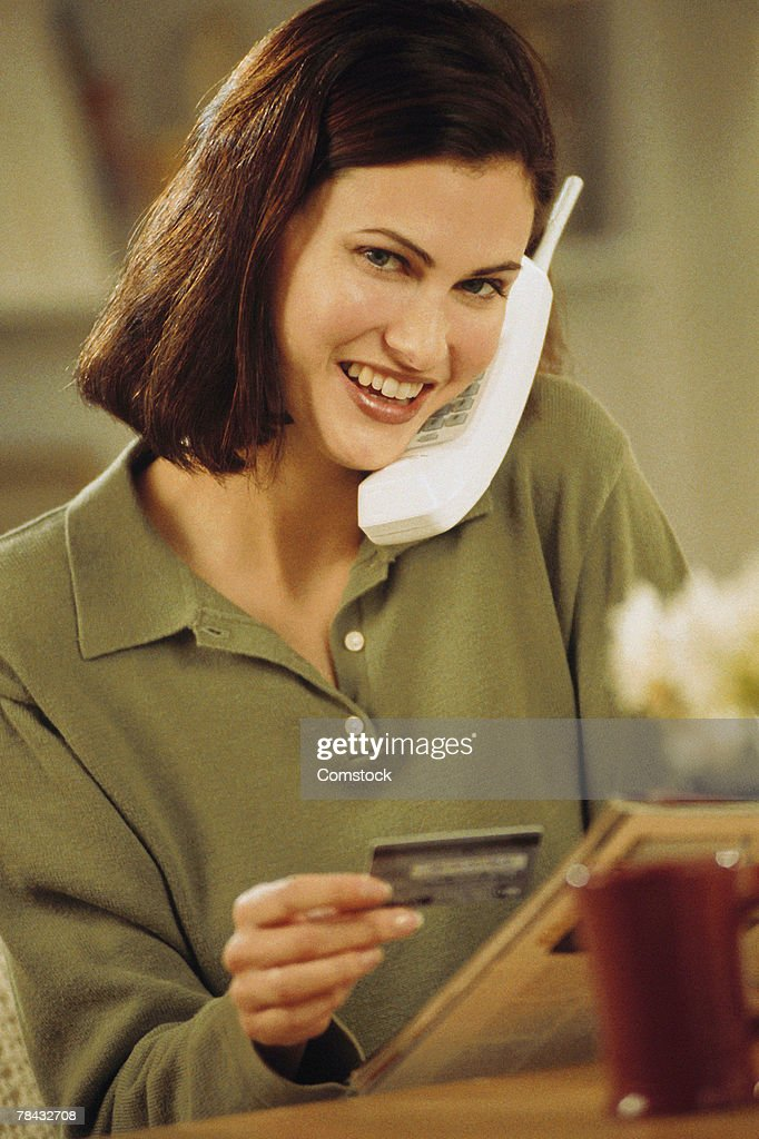 Woman ordering from catalog over the phone : Stockfoto