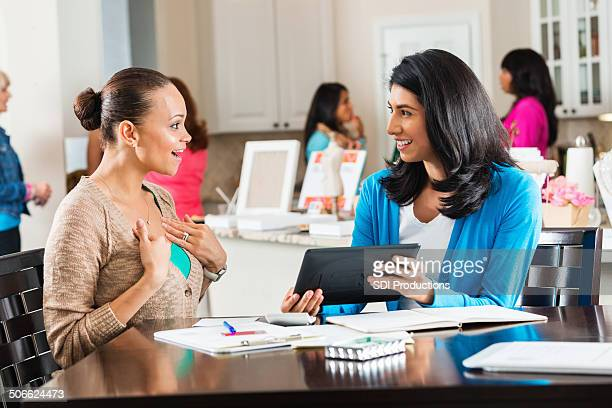 Woman ordering jewelry from salesperson at home boutique party