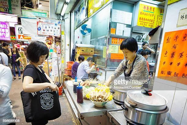 Woman ordering street food in Kowloon at night
