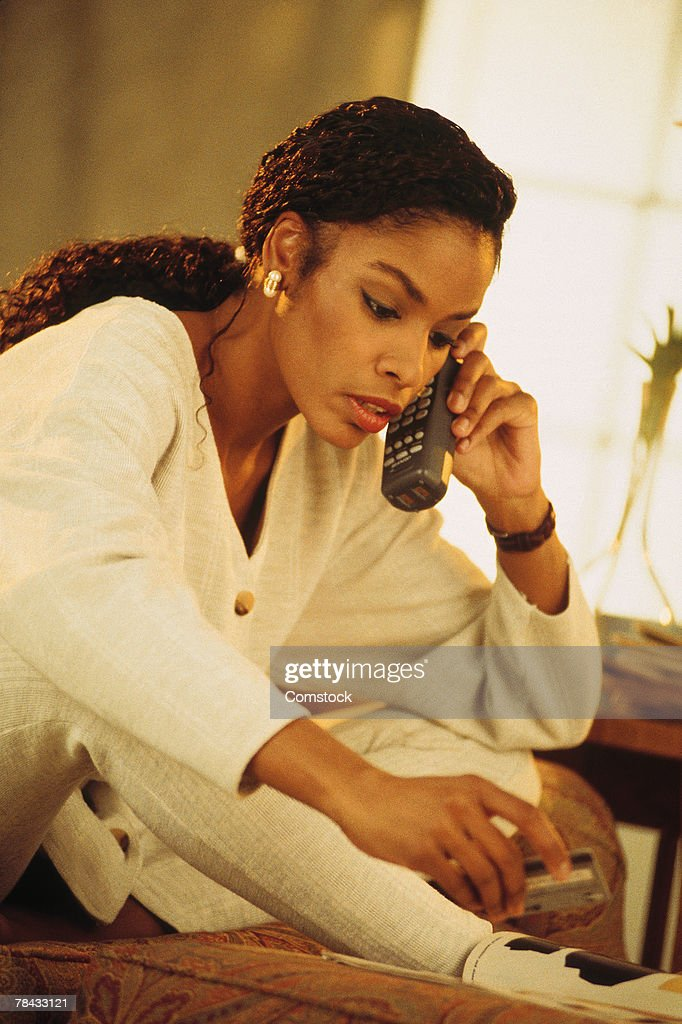 Woman ordering with credit card over the phone : Stockfoto