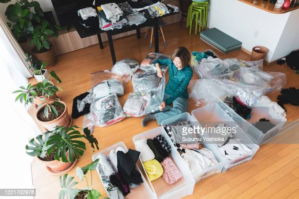 woman organizes clothes in living room of her home - arrangement stock pictures, royalty-free photos & images