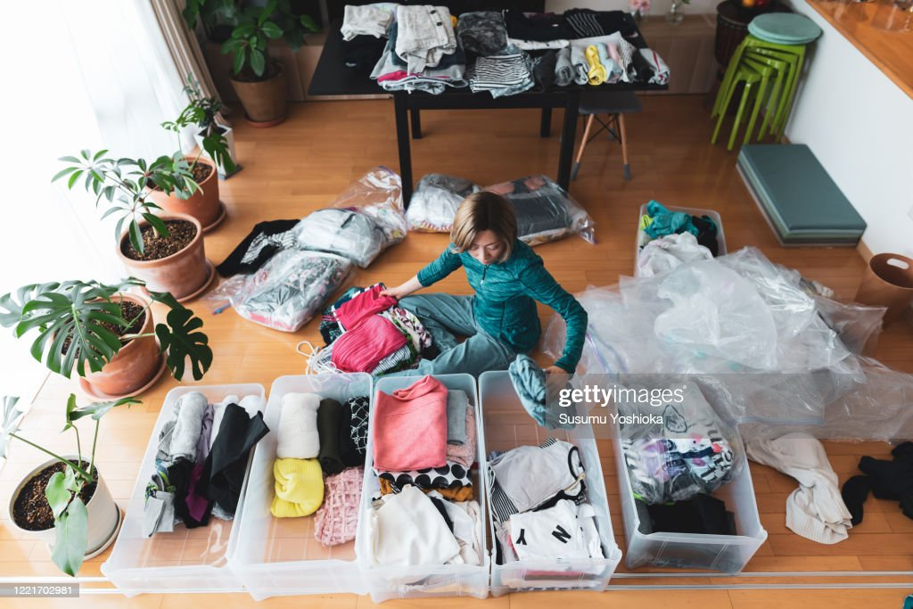 Woman organizes clothes in living room of her home : Photo
