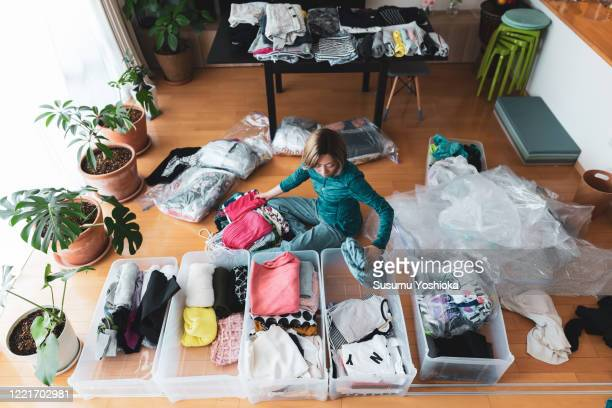 woman organizes clothes in living room of her home - storage compartment stock pictures, royalty-free photos & images