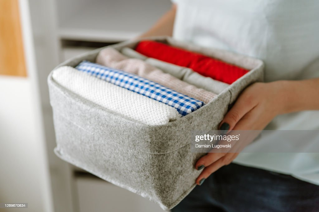 Woman organizing clothes in wardrobe, putting shirts in boxes, baskets into shelves. Clothes neatly folded after laundry. Concept of minimalist lifestyle : Stock Photo