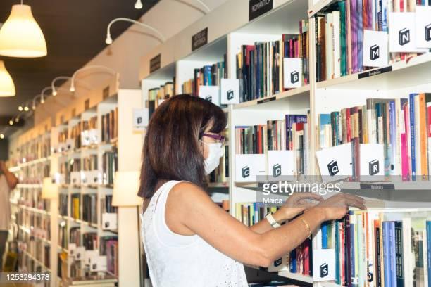 femme organisant l'étagère dans la librairie avec le protecteur - literature photos et images de collection