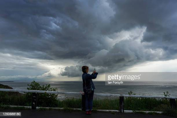 Woman out walking stops to take a picture on her phone as a storm cloud passes over the coast and out over the North Sea on June 19, 2020 in Saltburn...