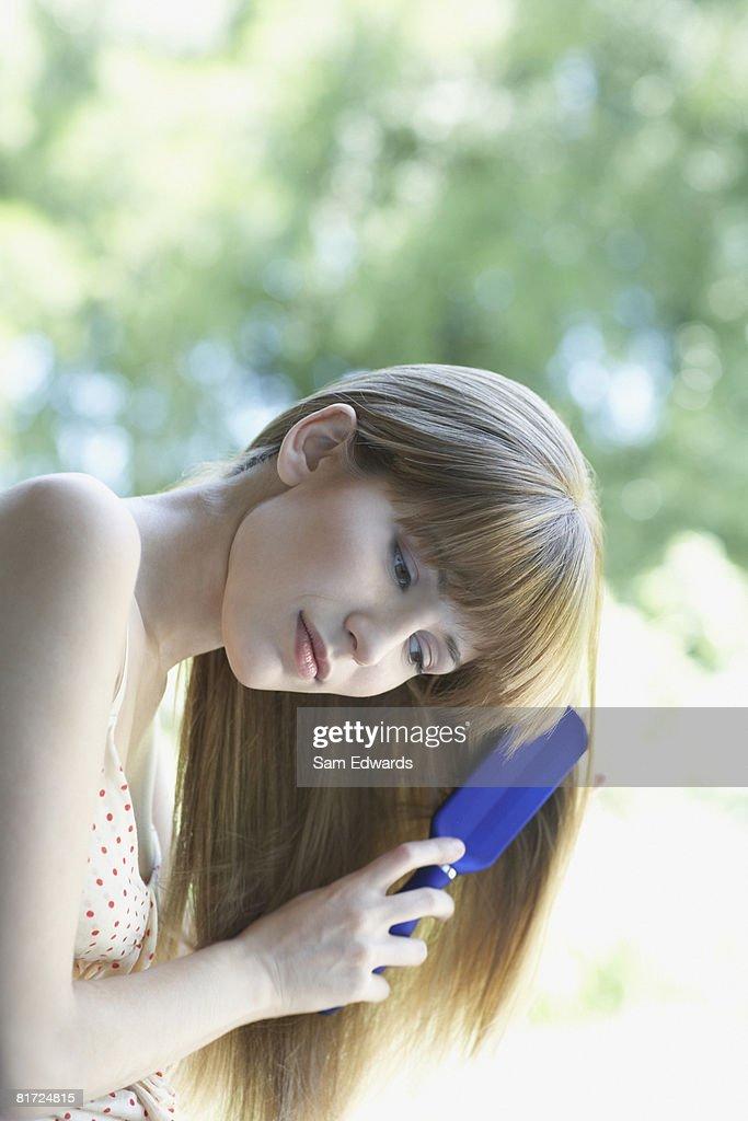 Woman outdoors brushing hair : Stock Photo