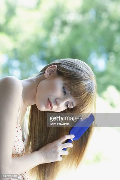 Woman outdoors brushing hair